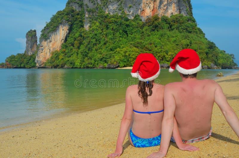 Праздники рождества и Нового Года на тропическом пляже, романтичной паре в шляпах santa сидя около моря стоковые фото