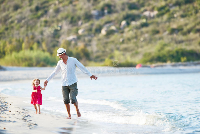 Праздники семьи Отец с маленькой девочкой на пляже моря стоковое фото