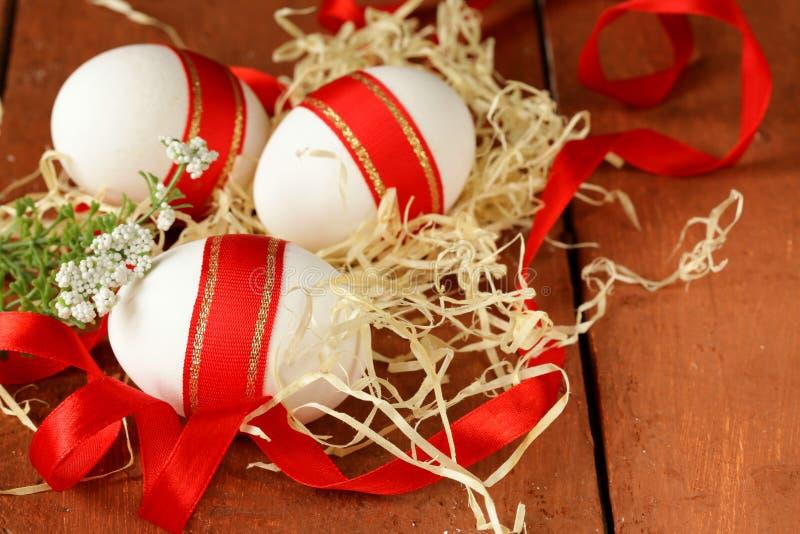 Праздничные яичка украшенные с красной лентой - символом пасхи стоковое фото