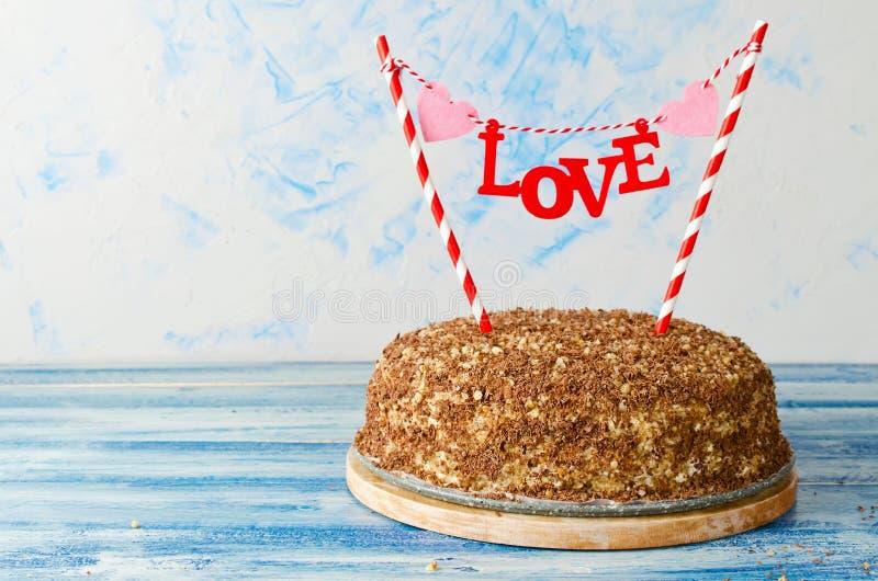 Праздничный торт с влюбленностью экстракласса на голубой предпосылке стоковые изображения