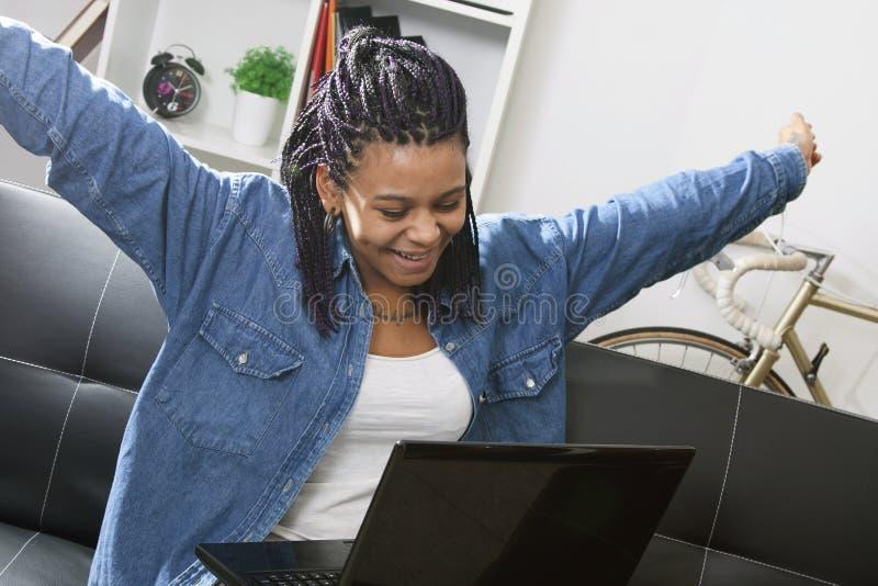 Праздновать женщину смотря компьтер-книжку стоковое фото