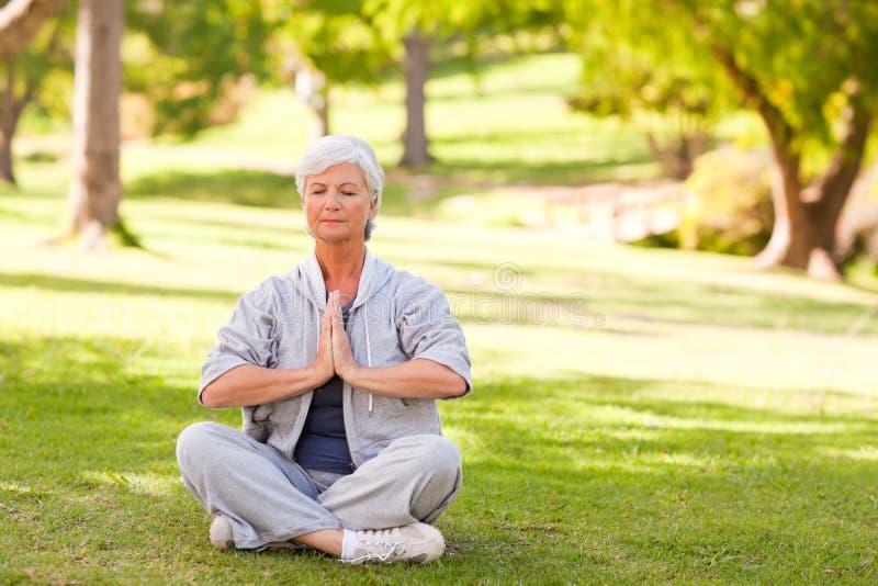 практикуя старшая йога женщины стоковая фотография
