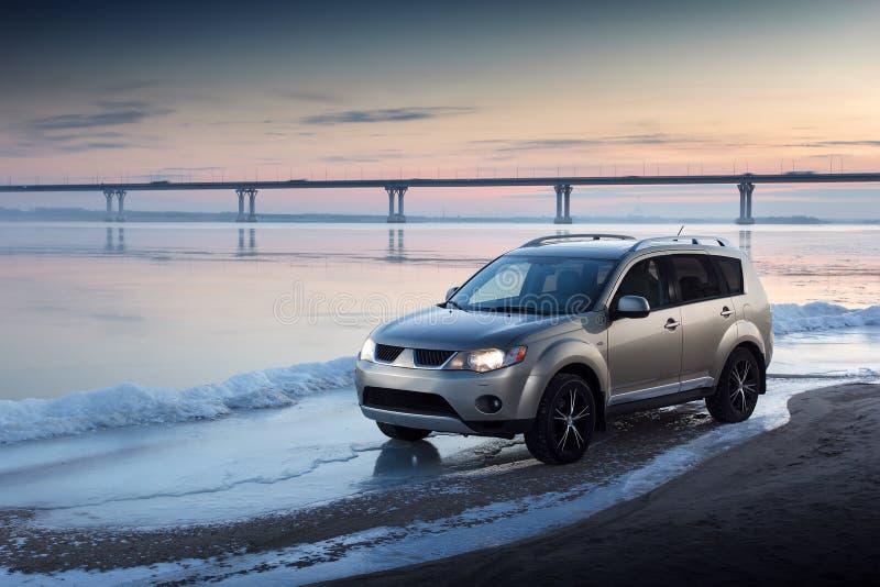 Пребывание автомобиля на побережье льда на заходе солнца зимы стоковая фотография rf