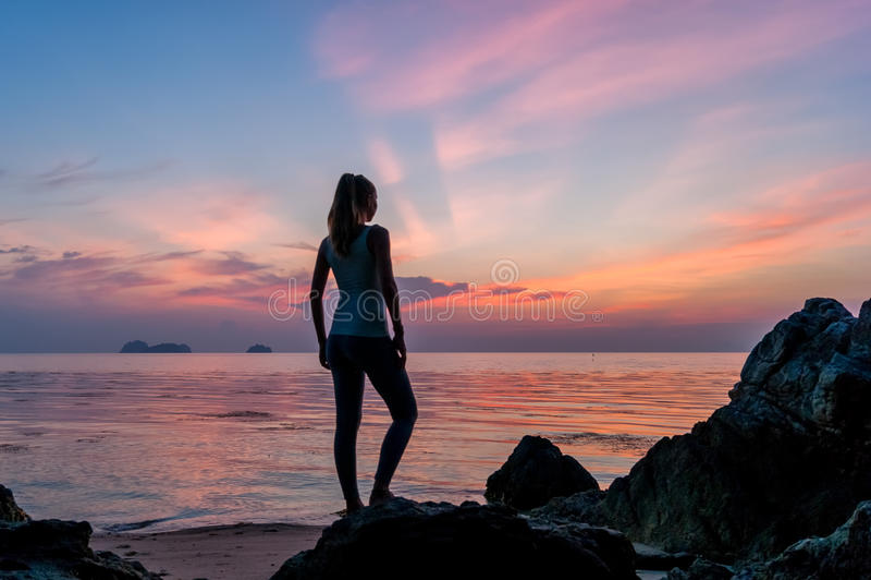 Пребывание маленькой девочки на пляже и наблюдать заход солнца стоковое фото rf