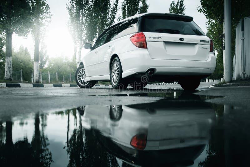 Пребывание наследия Subaru автомобиля на дороге асфальта и отраженное в лужице в городе на дневном времени стоковое фото rf