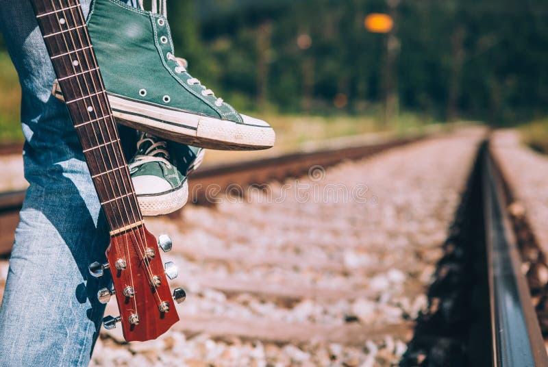 Пребывание путешественника человека на железной дороге - тапки и крупный план i гитары стоковые фотографии rf