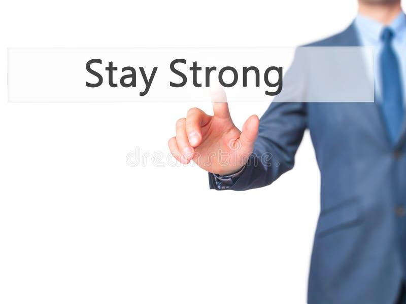 Пребывание сильное - кнопка отжимать руки бизнесмена на экране касания i стоковые изображения rf