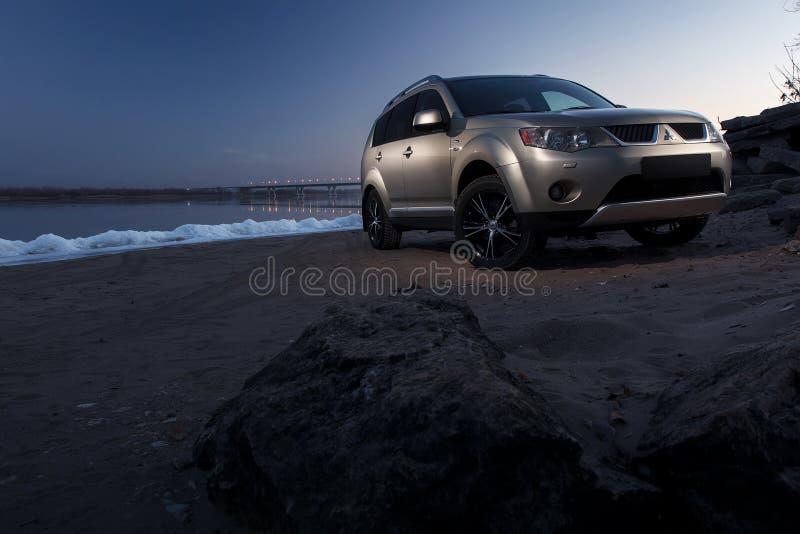 Пребывание Outlander Мицубиси автомобиля на побережье льда на заходе солнца зимы стоковые изображения