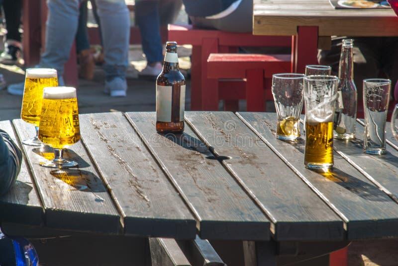 Превосходное светлое пиво на деревянном столе на славный день стоковое изображение