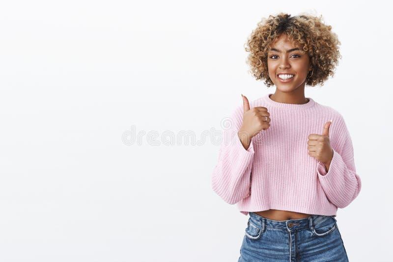 Превосходный, большие пальцы руки до вас Симпатичный поддерживающий и харизматический Афро-американский женский друг с белокурым  стоковые фотографии rf