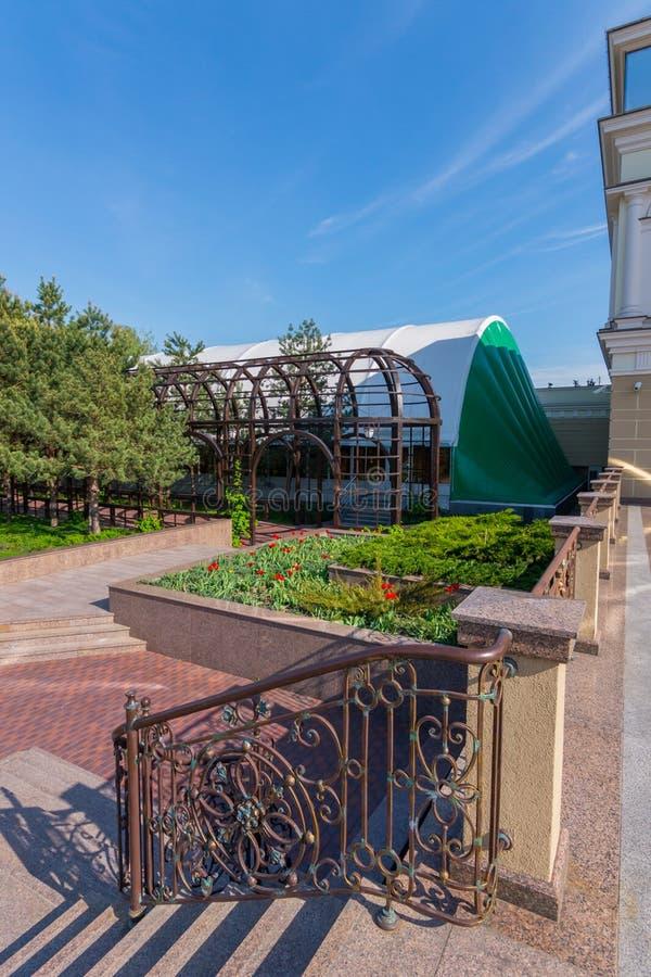 Превосходный ландшафт в парке с цветниками, деревьями и голубым небом Красивые курчавые перила около шагов только стоковое изображение