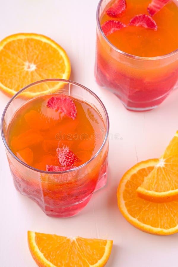 Превращайте в желе десерт с клубниками в стекле напитка с оранжевыми кусками рядом стоковые фото