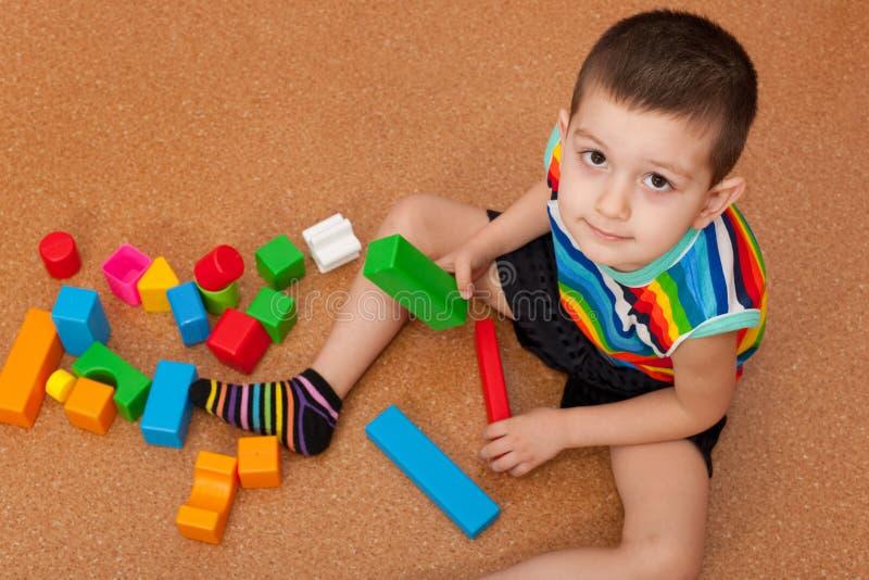 преграждает мальчика играя игрушку яркую стоковая фотография