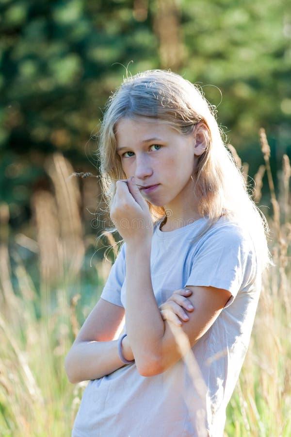 Предназначенная для подростков белокурая девушка на предпосылке луга лета стоковое фото rf
