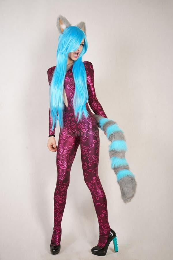 Предназначенная для подростков девушка в необыкновенном комбинезоне с ушами меха и длинным пушистым кабелем любит cosplay и стоит стоковое фото rf