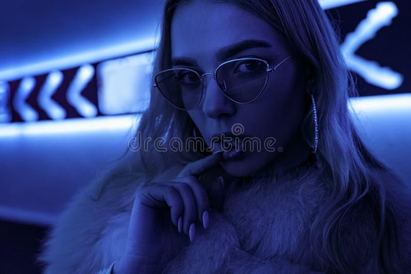 Предназначенная для подростков девушка в стильных стеклах в голубых неоновых светах подписывает на стене улицы, портрете стоковое изображение rf