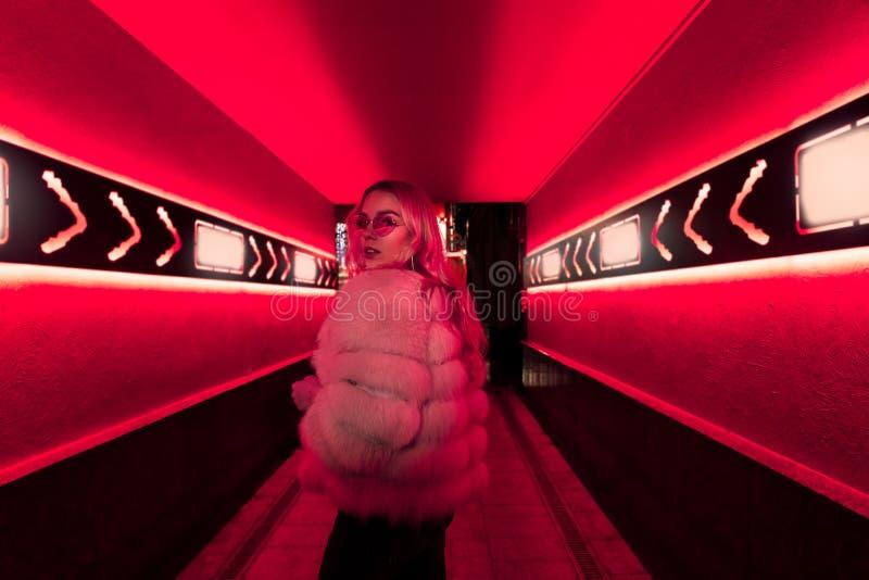Предназначенная для подростков девушка в стильных стеклах и мех в розовых неоновых светах подписывают на стене улицы стоковое изображение