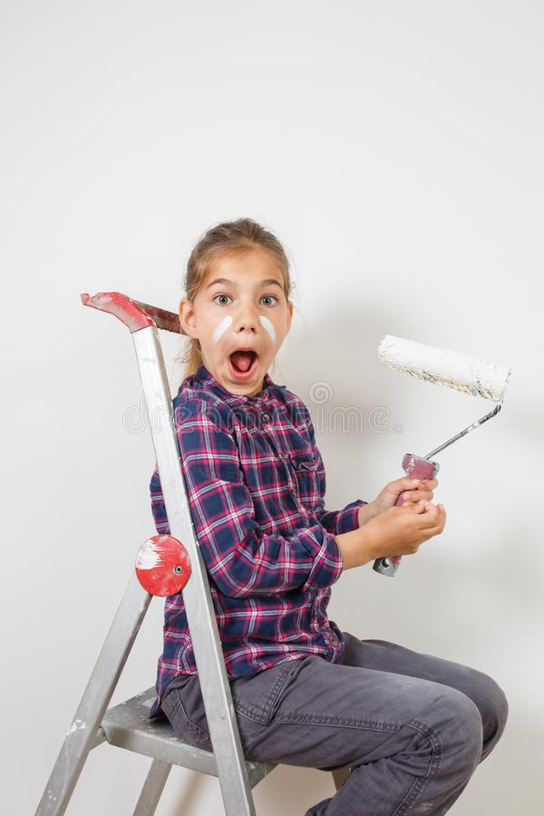 Предназначенная для подростков девушка на лестнице здания сотрясенной с щеткой для красить дальше стоковые фото