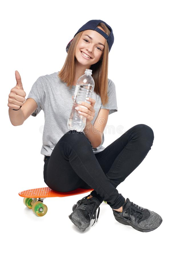 Предназначенная для подростков девушка сидя на доске конька с бутылкой воды стоковое фото