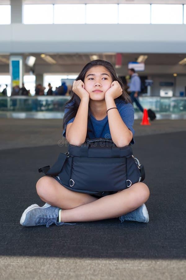 Предназначенная для подростков девушка сидя на поле авиапорта при багаж, отдыхая стоковые фотографии rf