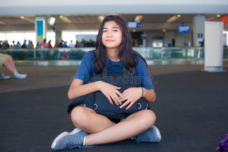 Предназначенная для подростков девушка сидя на поле на крупном аэропорте держа багаж стоковая фотография