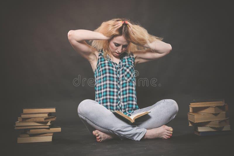 Предназначенная для подростков девушка сидя на поле рядом с книгами и эмоционально показывая ее ненависть, ненависть и усталость стоковая фотография