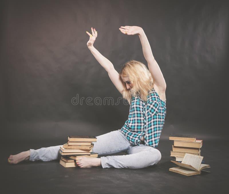 Предназначенная для подростков девушка сидя на поле рядом с книгами и эмоционально показывая ее ненависть, ненависть и усталость стоковые фото