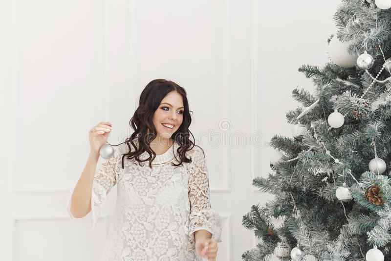 Предназначенная для подростков девушка украшая рождественскую елку стоковые фото