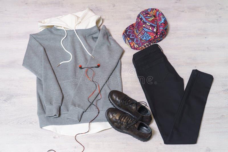 Предназначенная для подростков установленная одежда: серая фуфайка, черные джинсы, ботинки в milita стоковые фото