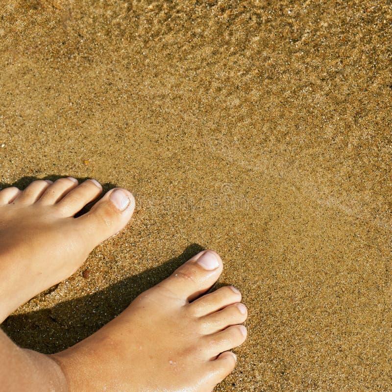 Предназначенные для подростков босые ноги девушки стоя на песке пляжа озера около воды стоковые изображения