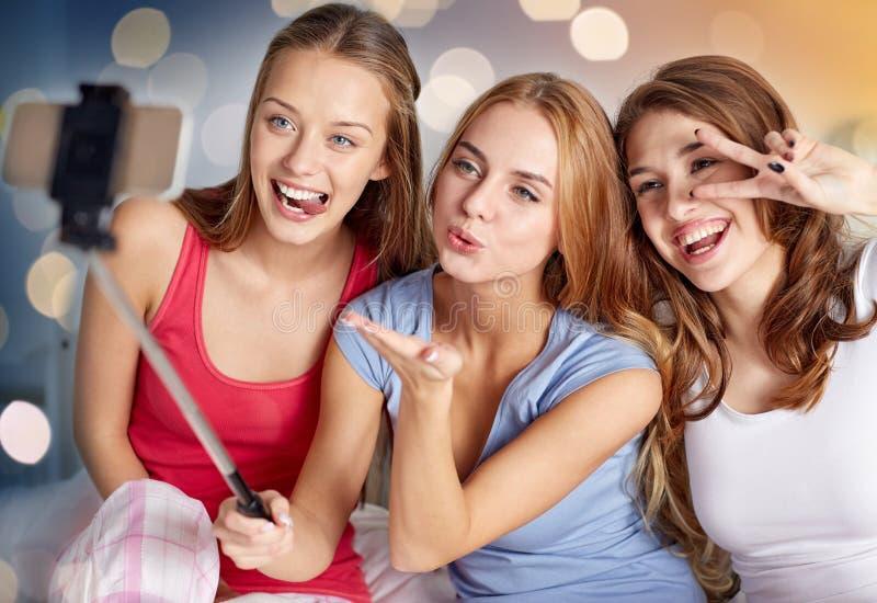 Предназначенные для подростков девушки при smartphone принимая selfie дома стоковые фотографии rf