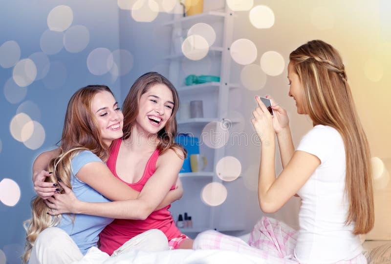 Предназначенные для подростков девушки при smartphone фотографируя дома стоковые фотографии rf