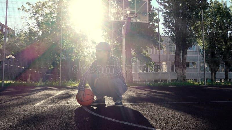 Предназначенный для подростков баскетболист мальчика с шариком outdoors стоковая фотография rf