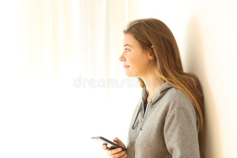 Предназначенный для подростков держа телефон смотря через окно стоковая фотография rf