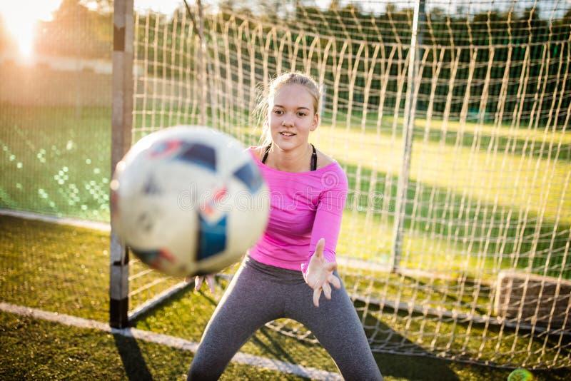 Предназначенный для подростков женский вратарь улавливая съемку стоковая фотография rf