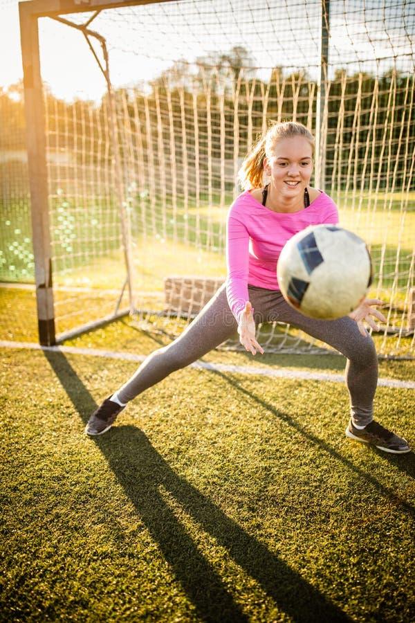 Предназначенный для подростков женский вратарь улавливая съемку стоковое фото