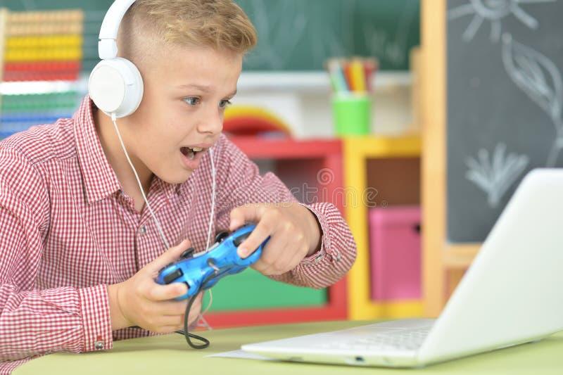 Предназначенный для подростков мальчик в наушниках играя компютерную игру стоковые фотографии rf