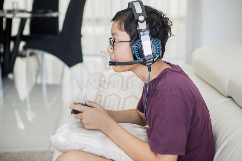 Предназначенный для подростков мальчик играя видеоигры с кнюппелем стоковые фотографии rf