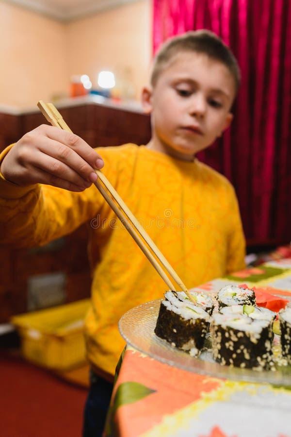 Предназначенный для подростков мальчик принимает крен суш плиты для еды стоковые фото