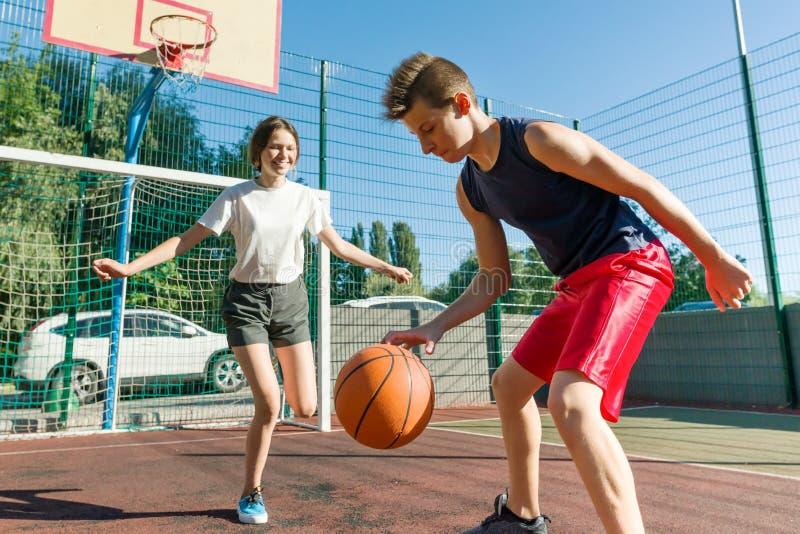 Предназначенный для подростков мальчик тренируя его подругу играя баскетбол, баскетбольный матч улицы стоковые изображения rf