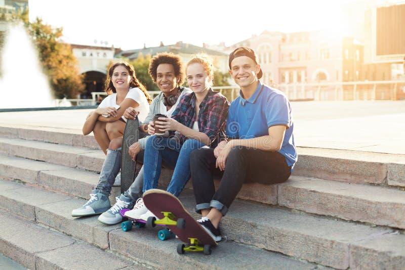 Предназначенный для подростков сидеть компании друзей на открытом воздухе, проводящ лето совместно стоковая фотография