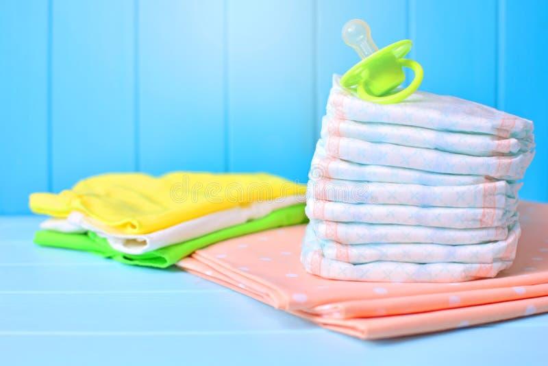 Предпосылка аксессуаров младенца Куча пеленок, одежд, салфеток и манекена стоковое фото rf