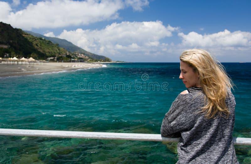 Предпосылка белокурой женщины внешние, лазурные голубые моря, пляж и mountan стоковое фото rf