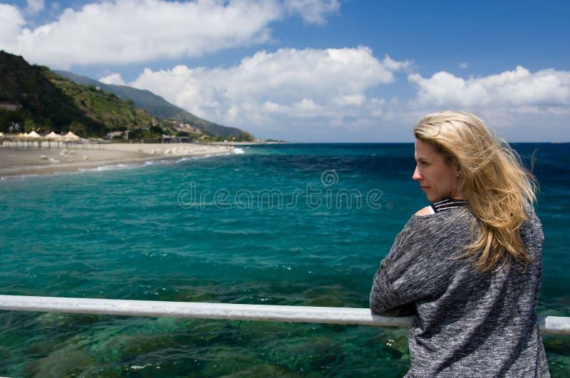 Предпосылка белокурой женщины внешние, лазурные голубые моря, пляж и mountan стоковое изображение rf