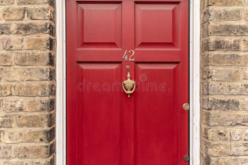 Предпосылка винтажного красного покрашенного взгляда виньетки двери и knocker сделанного из старомодного винтажного латунного мет стоковое изображение