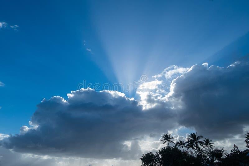 Предпосылка голубого неба с пушистыми белыми облаками и лучами солнечного света стоковые изображения rf