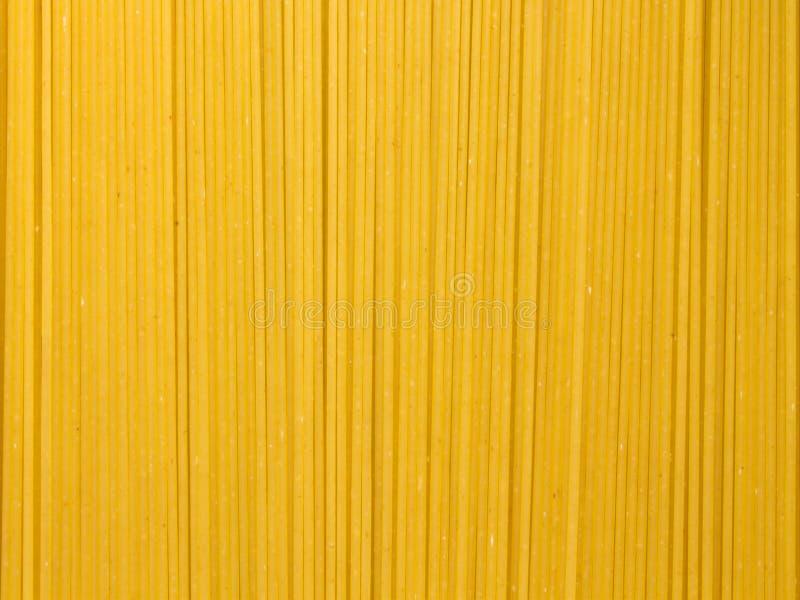 Предпосылка длинных сырцовых желтых макаронных изделий спагетти в плоскости вертикальное  стоковые изображения