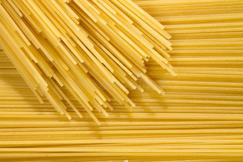 Предпосылка длинных сырцовых желтых макаронных изделий спагетти в плоскости горизонтальное, и много макароны на верхней части стоковое фото rf