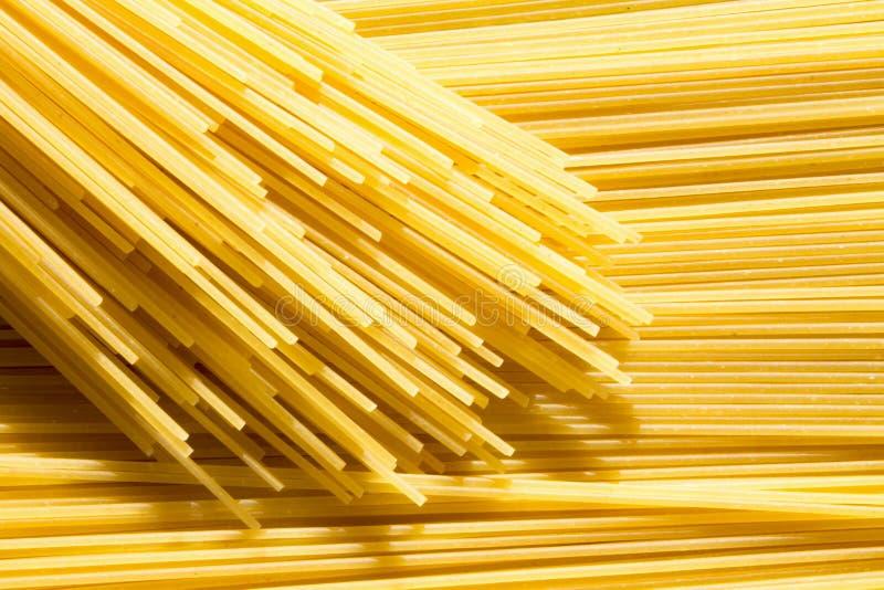 Предпосылка длинных сырцовых желтых макаронных изделий спагетти в плоскости горизонтальное, и bandle макарон на верхней части стоковое изображение