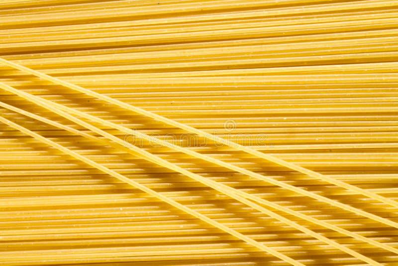 Предпосылка длинных сырцовых желтых макаронных изделий спагетти в плоскости горизонтальное, и некоторые макароны на верхней части стоковые фотографии rf